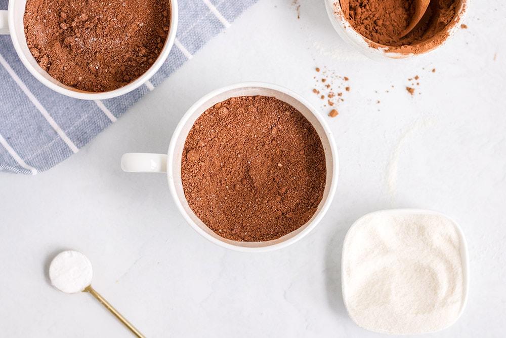 cocoa powder in a mug next to other mug cake ingredients