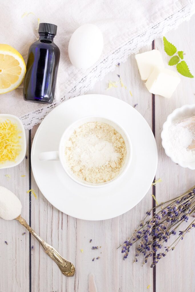 dry ingredients in mug with dried lavender, lemon, and other ingredients on table