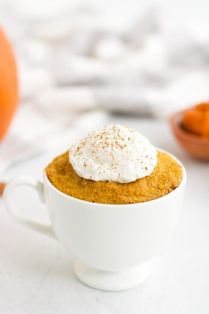 keto pumpkin mug cake in a white mug topped with whipped cream