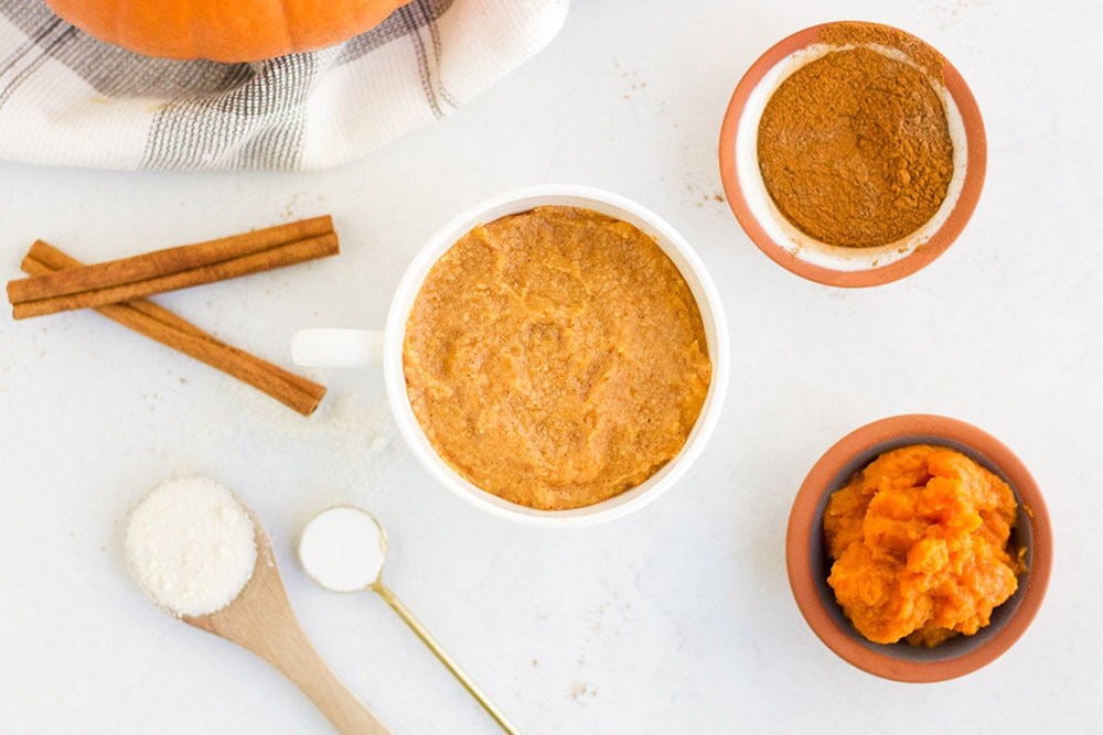 pumpkin mug cake batter in a mug surrounded by ingredients