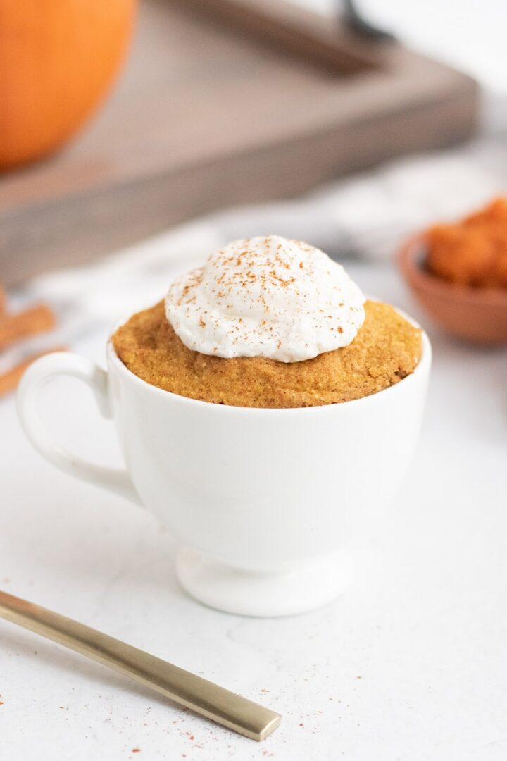 pumpkin cake in a mug by a fork and a tray