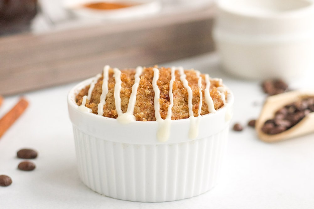 Coffee cake in a ramekin on a white table with coffee beans