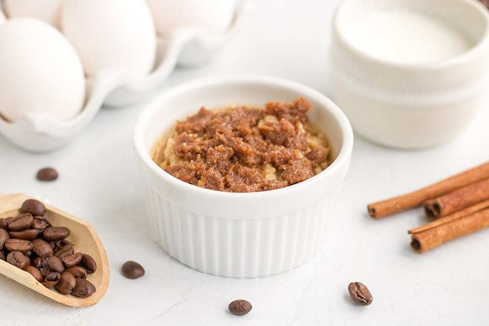 Crumbled topping on top of batter in a dish for coffee mug cake