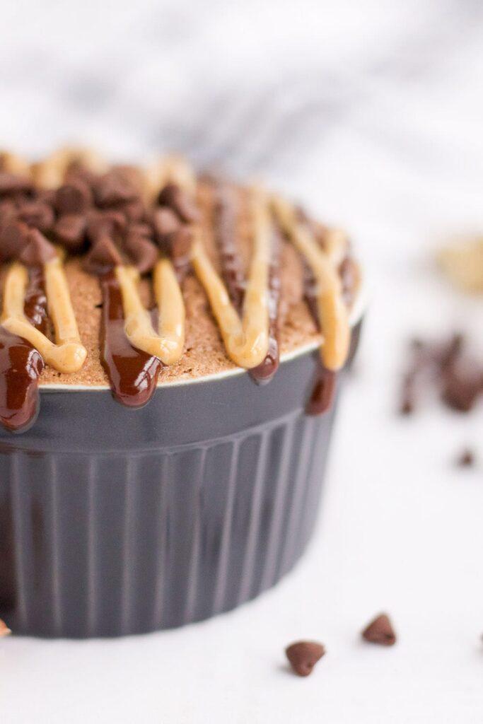 Peanut butter chocolate mug cake in a ramekin by mini chips.