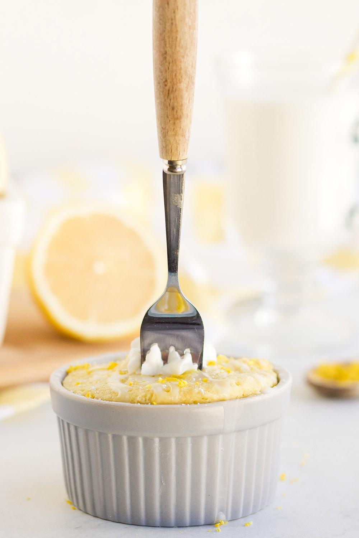 Fork stuck in a lemon cake in a grey ramekin.