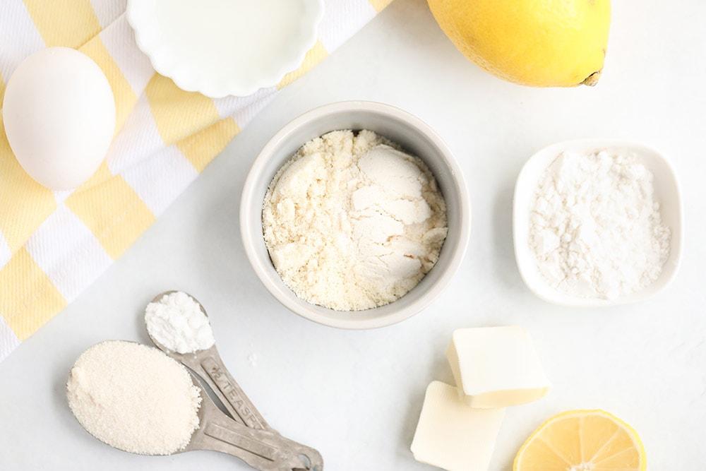 Ingredients for lemon mug cake in bowls on a table.