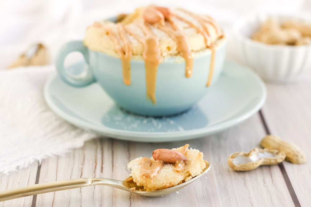 Peanut butter mug cake in a light blue mug with a spoonful in front of it.