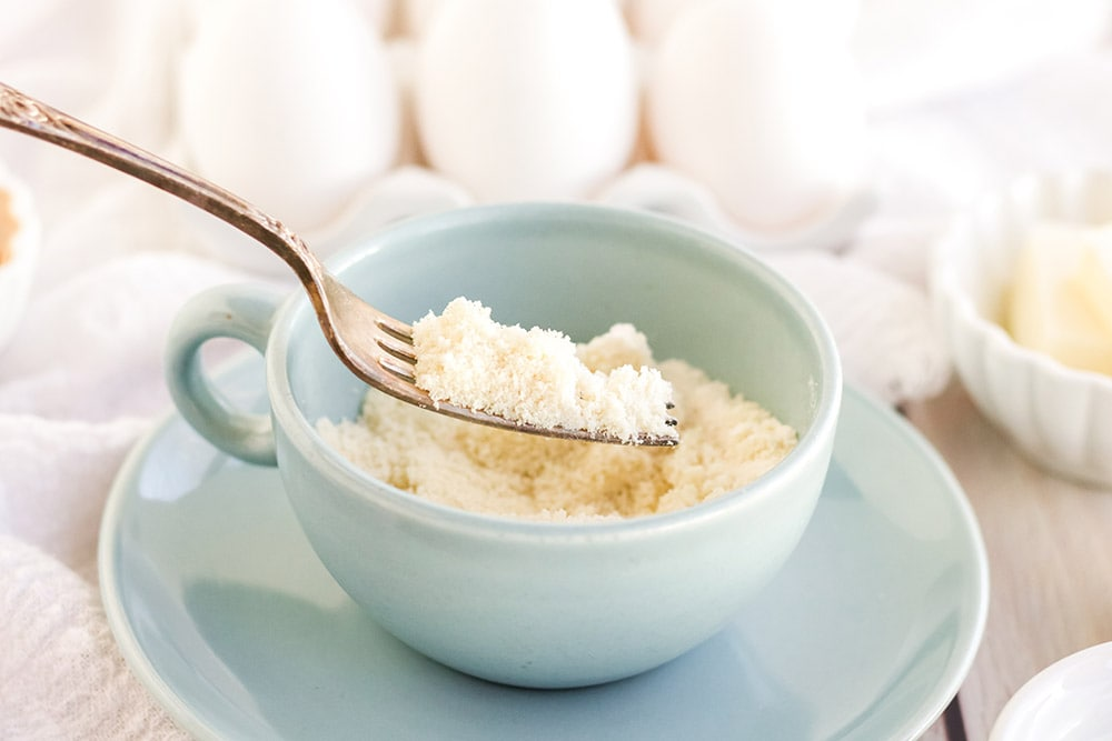 Dry ingredients for mug cake in a light blue mug.
