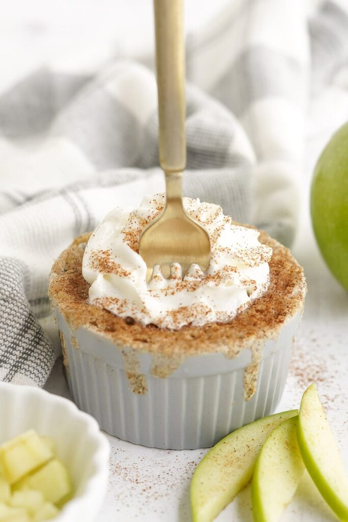 Fork in a cake in a small dish. There are green apples and slices on the table with a gray napkin.