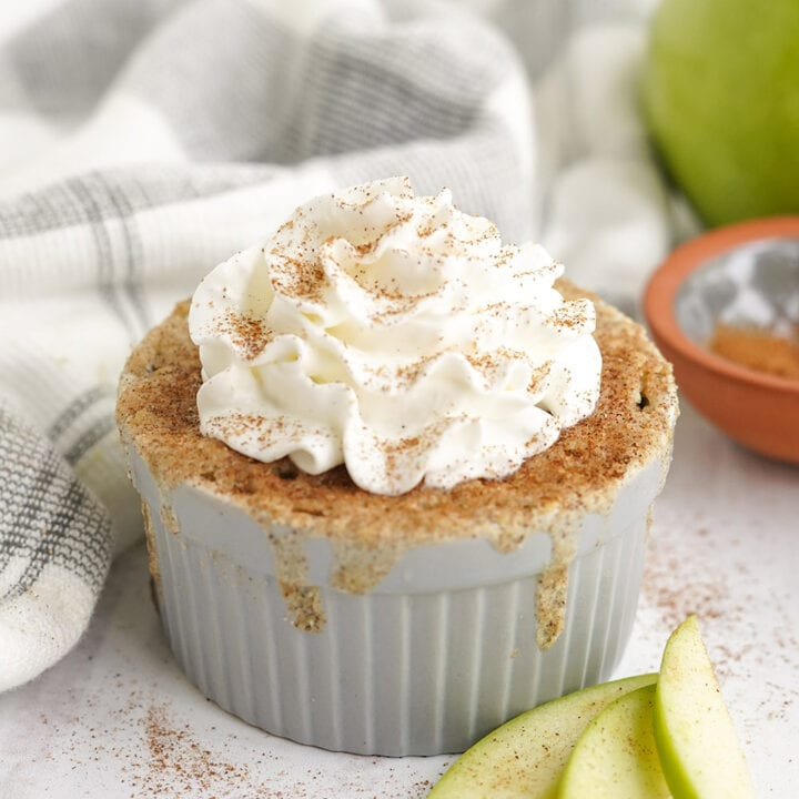 Cake topped with cinnamon and whipped cream in a gray dish with apple slices on the table.