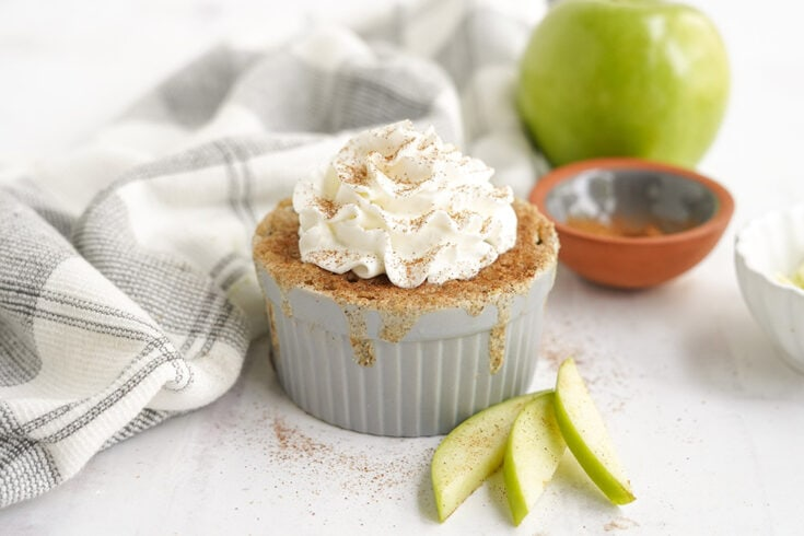 Apple cake in a ramekin topped with whipped cream and cinnamon. Apples and a napkin on the table.