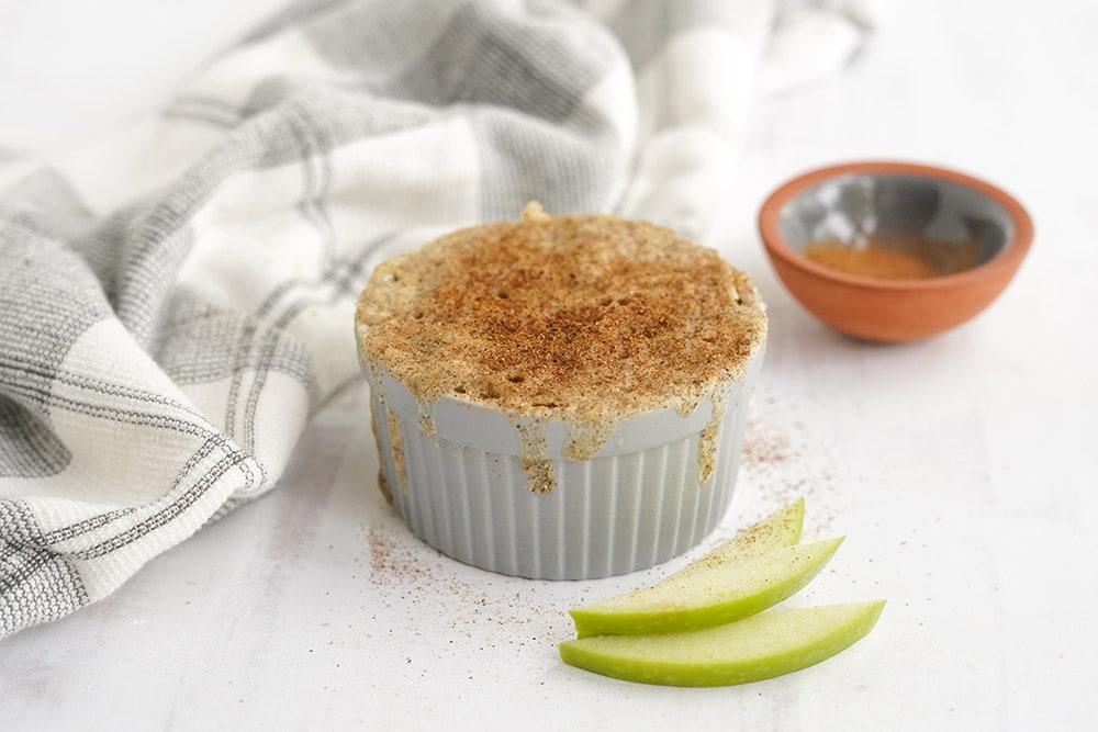 Small apple cake topped with cinnamon in a gray ramekin.