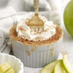 Fork stuck in an apple mug cake with whipped topping and cinnamon.