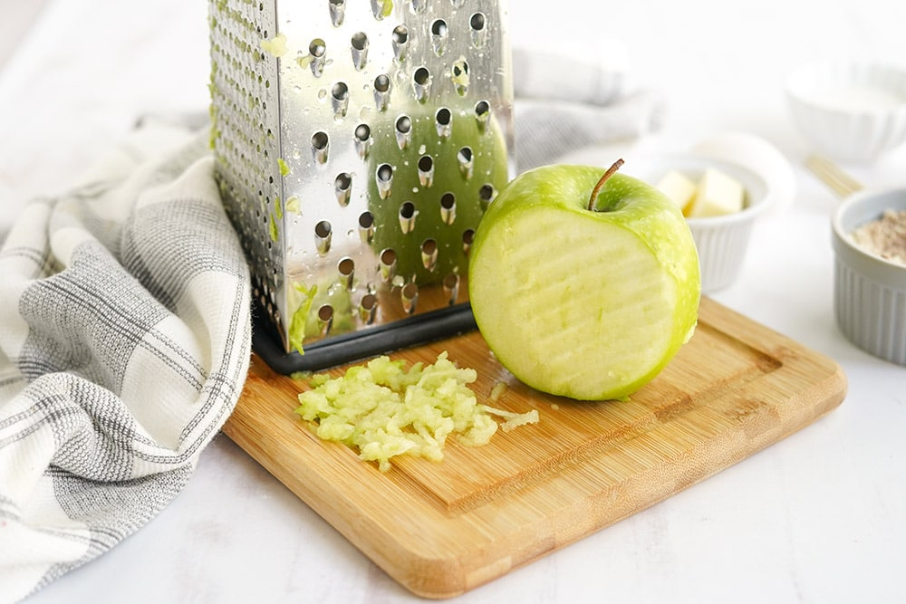 Green apple with a shredder on a board.