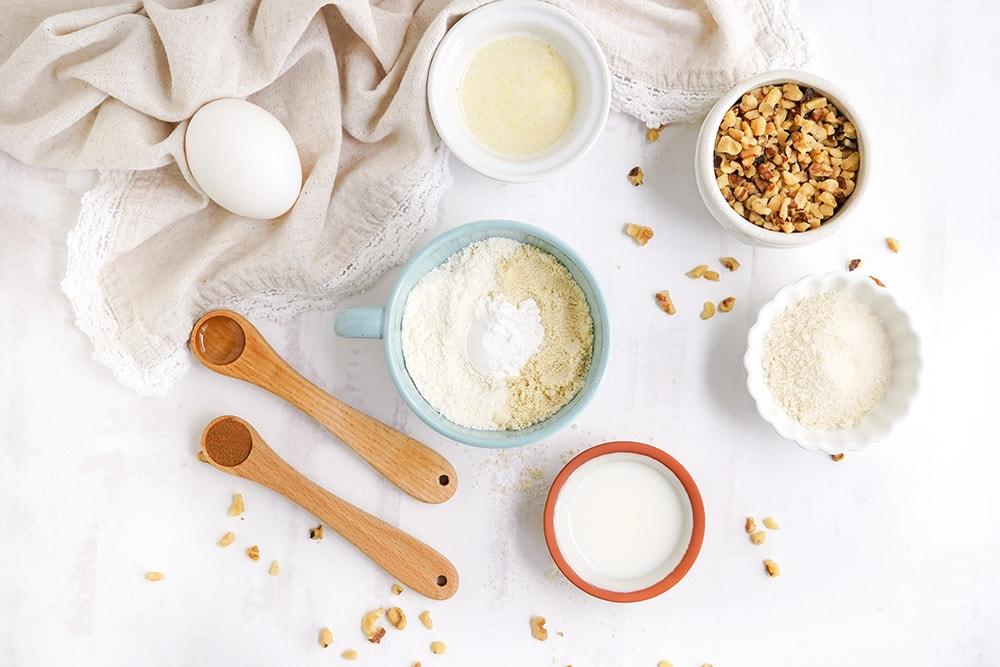 Bowls of ingredients to make a keto banana mug cake on a table.