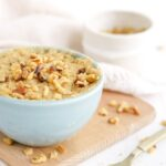 Banana cake in a mug topped with nuts and more chopped nuts on the table.