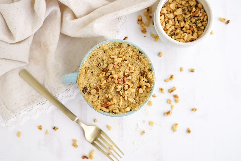 Banana cake topped with walnuts with chopped walnuts and a gold fork on the table.