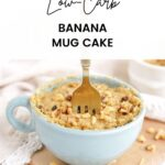 Light blue mug cake with banana and walnut with a fork stuck in it sitting on a board.