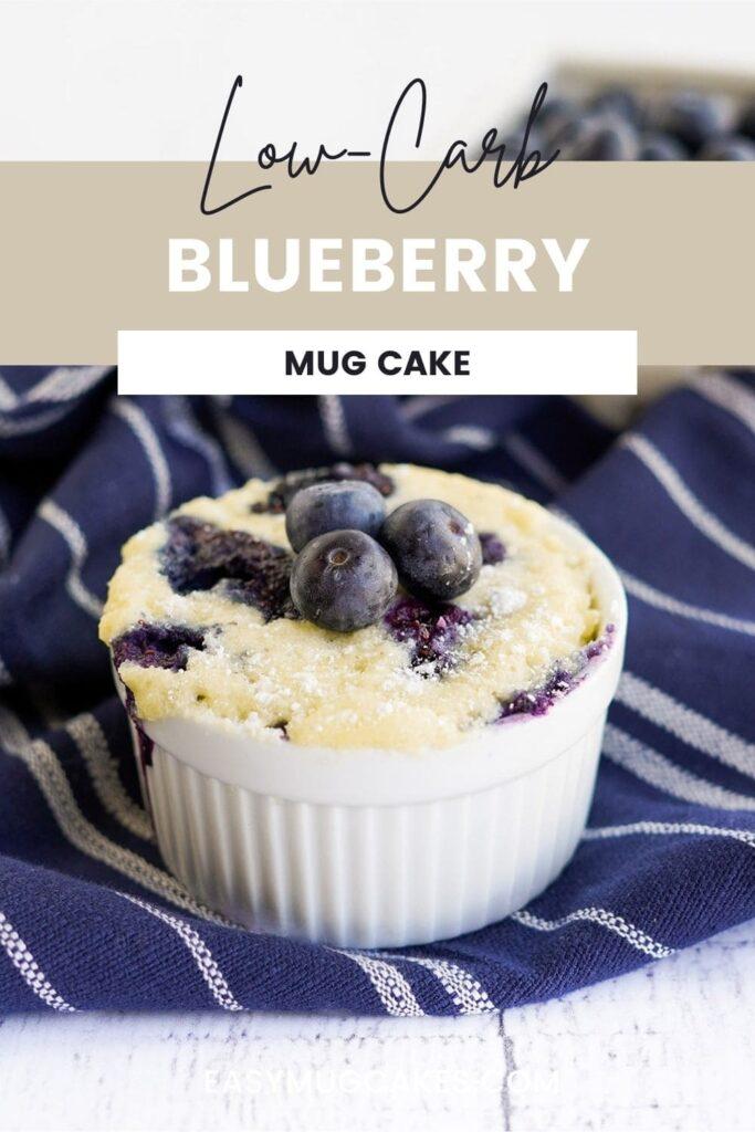 Blueberry mug cake in a white ramekin on a blue napkin.