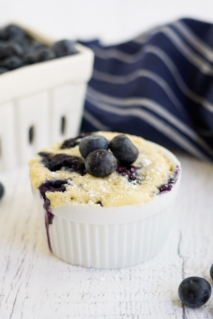 Fresh blueberries on top of a small cake in a white dish.