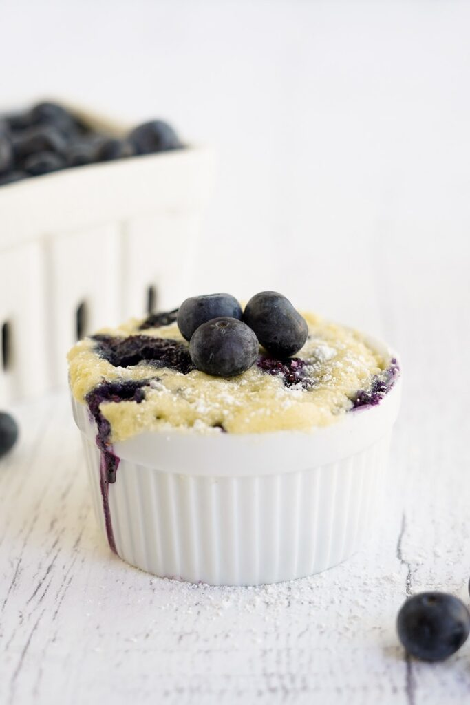 Blueberry cake in a mug with basket of berries on the table.