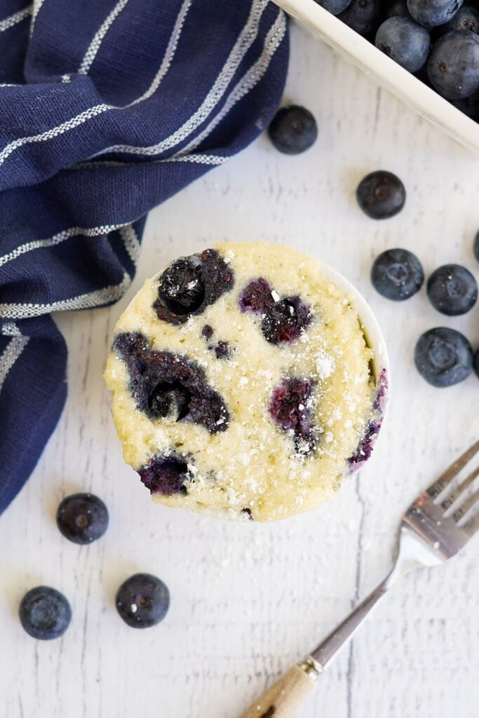 Overhead shot of blueberry cake in a mug with a fork and more berries on the table.