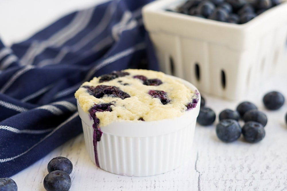 Tiny baked cake in a white dish with blueberries.