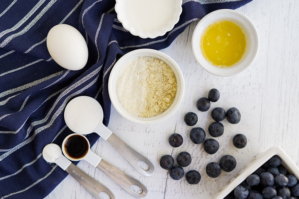 Flat lay of ingredients to make blueberry cake on a table with a blue napkin.
