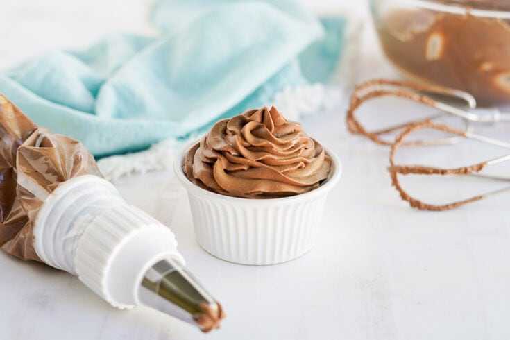 Chocolate topping in a white dish with the piping bag and mixer next to it.