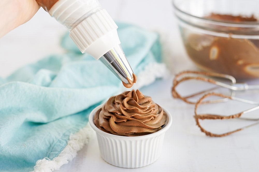 Piping chocolate topping into a dish.