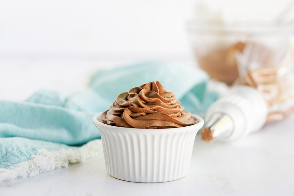 Chocolate whipped topping in a white dish with the piping bag and a light blue napkin on the table.
