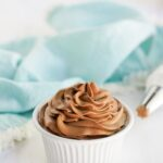 Dish of cocoa whipped topping on a table with a blue napkin.