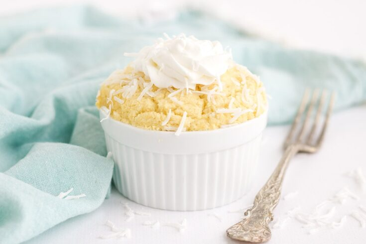 White ramekin with coconut cake topped with whipped cream next to a blue napkin and fork.