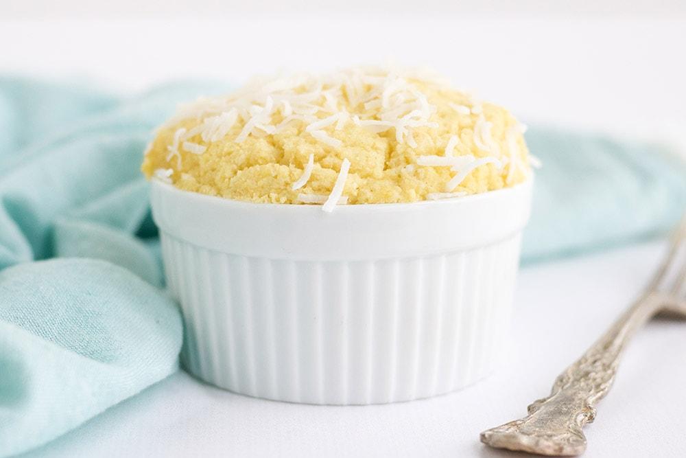 Coconut mug cake in a white ramekin topped with shreds.