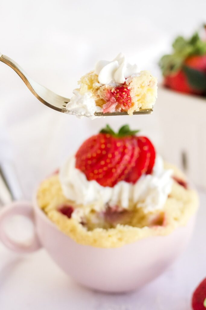 Fork with cake on it raised above strawberry cake in a mug.