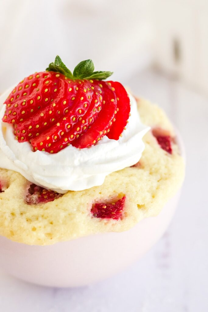Close shot of a mug cake with sliced strawberries and whipped topping.