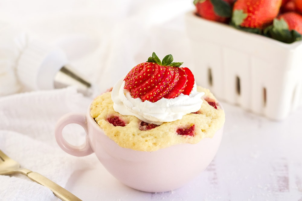 Cake with strawberries and whipped cream in a pink mug.