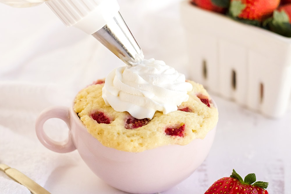 Piping whipped cream on top of a strawberry cake in a pink mug.