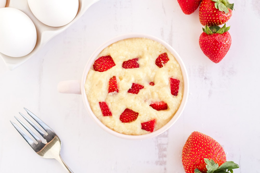 Pieces of strawberry in the batter of a cake in a pink mug.